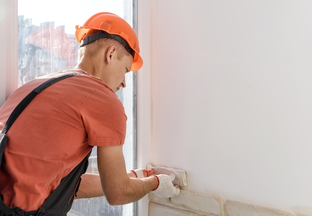 Рабочий кладет на стену гипсовую плитку.