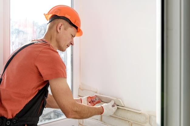 작업자는 벽에 석고 벽돌 타일을 설치하고 있습니다.
