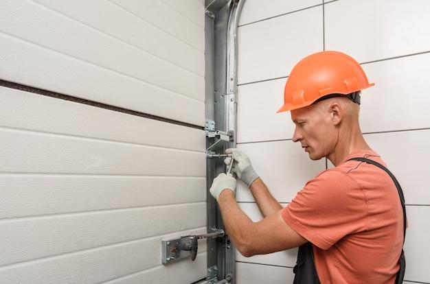 Рабочий устанавливает лифтовые ворота в гараже.