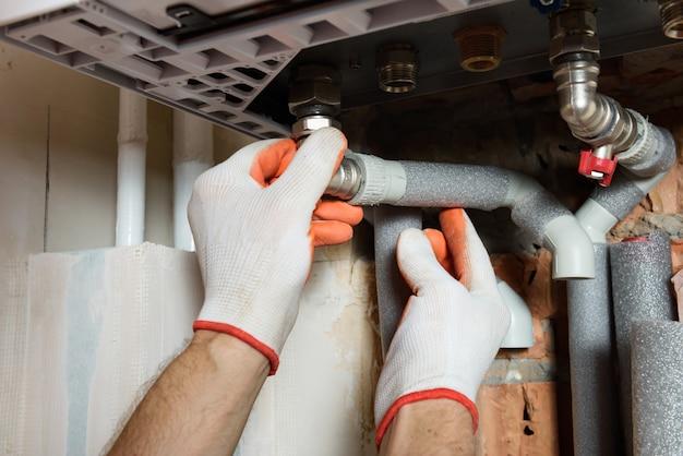 Рабочий устанавливает трубы газового котла.
