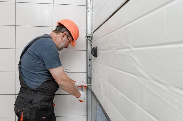 Рабочий устанавливает подъемные ворота гаража.
