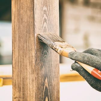 Рабочий красит деревянную террасу