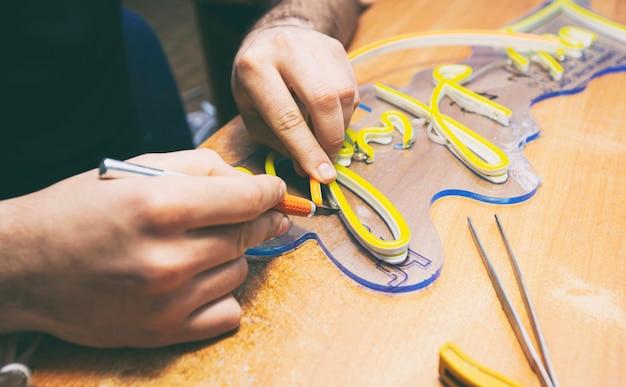 작업자는 led 네온 리본으로 만든 간판을 생산합니다.