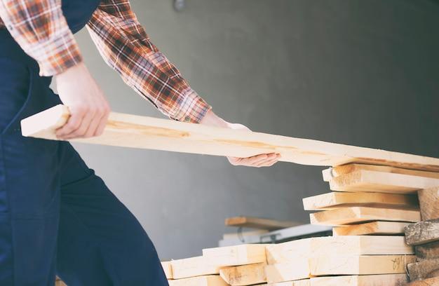労働者は材木の山から木の板を取っています