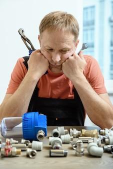 Рабочий думает и смотрит на элементы водопровода.