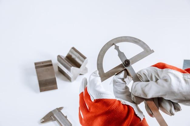 Рабочий измеряет угол металлического изделия транспортиром.