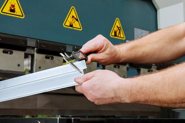 Рабочий измеряет изделие после гибки на гидравлическом прессе для гибки листового металла.