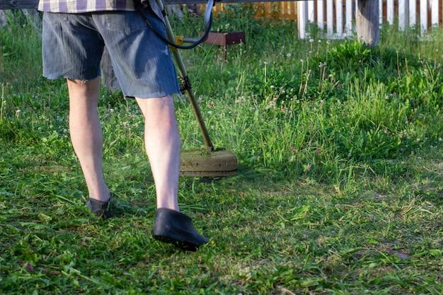 庭の労働者は草を刈り取ります。一般労働者の制服を着た男は芝生で働いている。領土の改善に関する地方自治体のサービスの仕事。