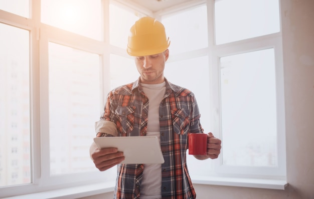 Рабочий или строитель держит в руках чашку кофе и смотрит на планшет. на фоне строительства и ремонта.