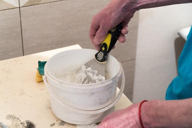 Рабочий готовит в ведре шпаклевку для швов плитки технология укладки плитки