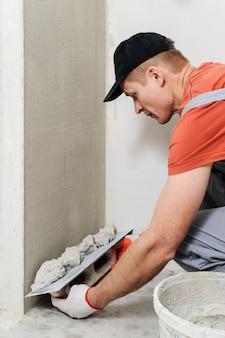 Рабочий кладет штукатурку на стену