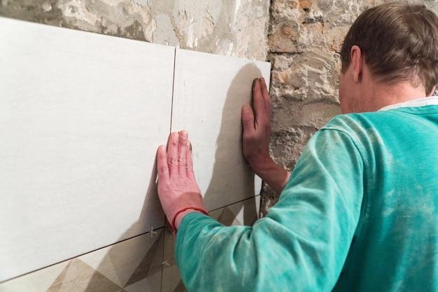 Рабочий кладет плитку на стену. отделочные работы, размытый фокус. технология укладки плитки.