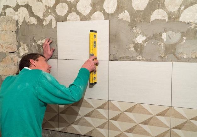 労働者は壁にタイルを置きます。仕上げ作業、ぼやけた焦点。タイルを敷く技術。