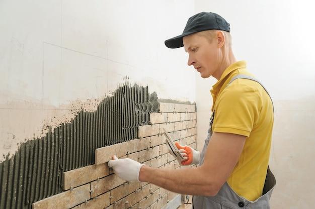 Рабочий кладет плитку в виде кирпича на стену