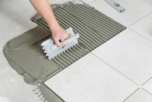 Рука рабочего наносит клей для плитки на стену зубчатым шпателем.