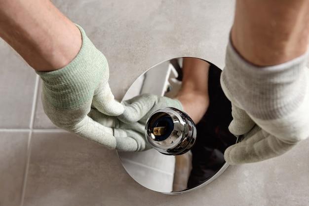 Руки рабочего монтируют встраиваемый кран.