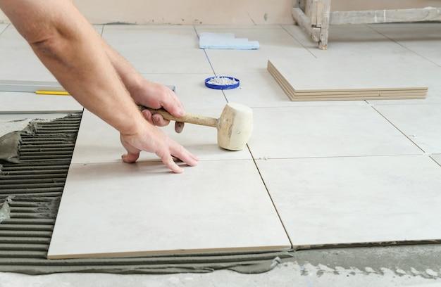 Рабочий стучит резиновым молотком по плитке для лучшего приклеивания