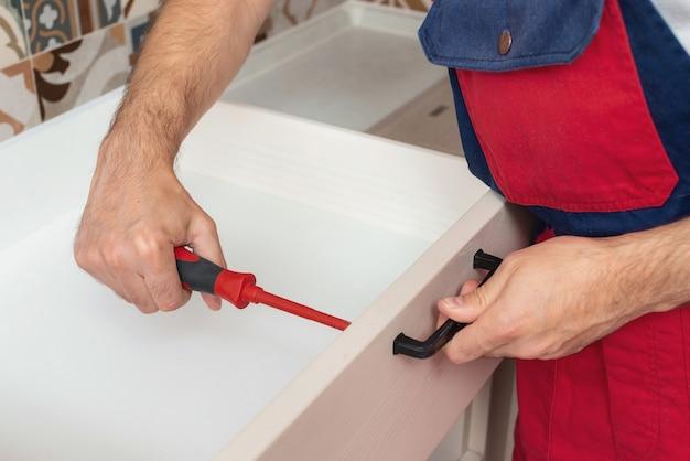 Рабочий устанавливает новую ручку на белый шкафчик с помощью отвертки.