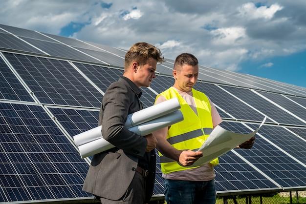작업자는 그의 상사에게 녹색 에너지의 개념인 태양 전지판을 설치하는 방법을 알려줍니다.