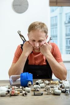 Рабочий думает и смотрит на элементы сантехники