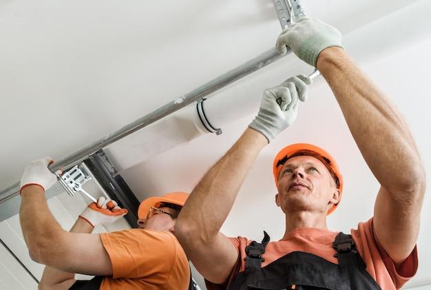 노동자들은 차고에 리프트 게이트를 설치하고 있습니다.
