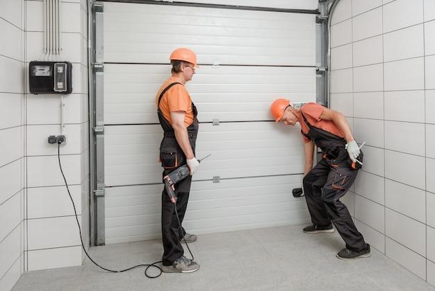 Рабочие устанавливают лифтовые ворота в гараже.