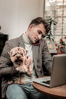 작업 과정. 일하는 동안 개를 안고 바쁜 남자