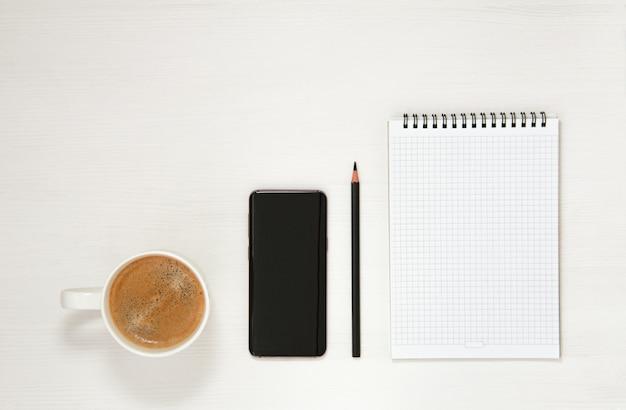 メモ帳、電話、鉛筆、一杯のコーヒーのある職場は、真っ白な背景に置かれています。フラットスプーン、上面図。