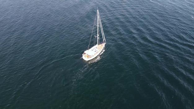 ヨットは青い海を航行します。公海で晴れた日に休んでください。ドローンの航空写真。