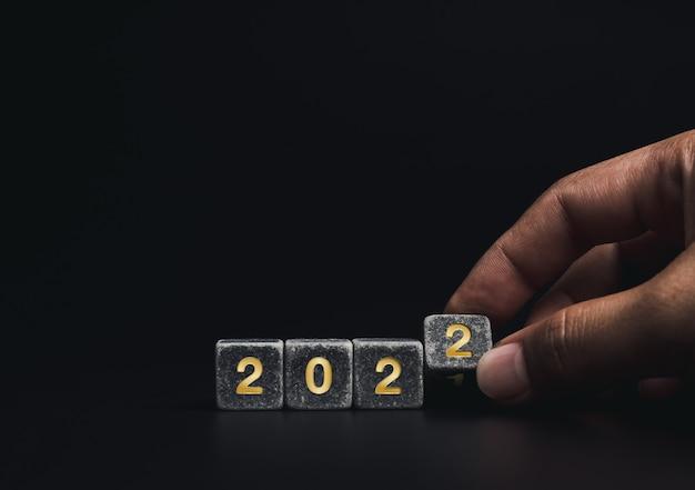 2021年は成功したコンセプトで2022年に変わります。コピースペース、最小限のスタイルで暗い背景に2021年から2022年に黄金の数字を変更するためのクローズアップの手反転黒い立方体ブロック。
