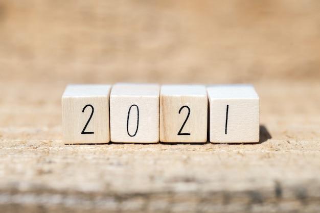 2021 год, написанный на деревянных кубиках, новогодней концепции или поздравительной открытке. деревянный стол