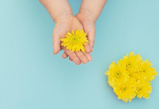 花のぼやけた花束と青い背景の上の子供の手の黄色い花