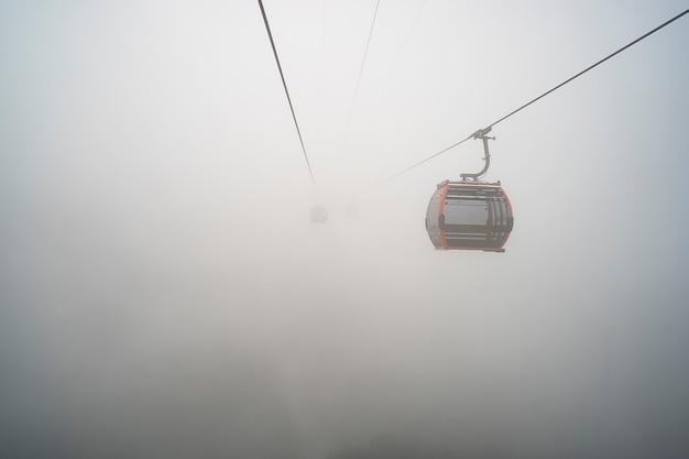 黄色いケーブルカーが霧の空に昇ります。山のケーブルカーは霧の日。