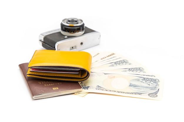 黄色いお金の財布はパスポートに置かれ、紙幣とカメラは白い表面にありました。孤立。