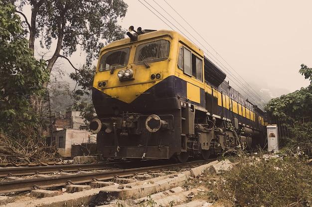 黄色い列車は砂漠を鉄道で行きます。インドの列車-ローカル列車。インドの州、村