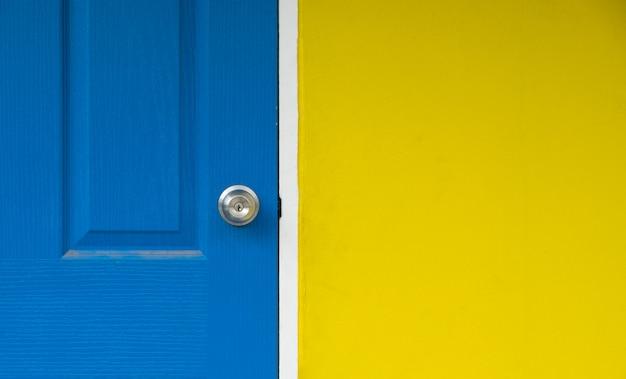 노란색 벽과 배경에 대한 파란색 문을 닫고 파란색 문이 잠겨 있습니다.