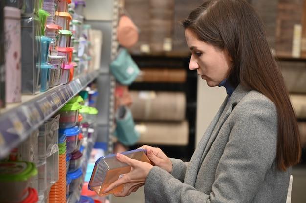 Юная брюнетка выбирает пластиковые контейнеры для хранения еды в магазине.