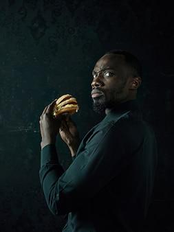 ハンバーガーを食べて、黒いスタジオで目をそらしている若いアフリカ系アメリカ人の男