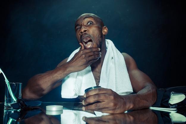自宅でひげをひっかいた後、鏡の前に座っている寝室の若いアフリカ人。人間の感情の概念。アフターシェーブクリームのコンセプト