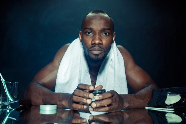 Молодой африканец в спальне сидит перед зеркалом после того, как почесал бороду дома. концепция человеческих эмоций. кремы после бритья