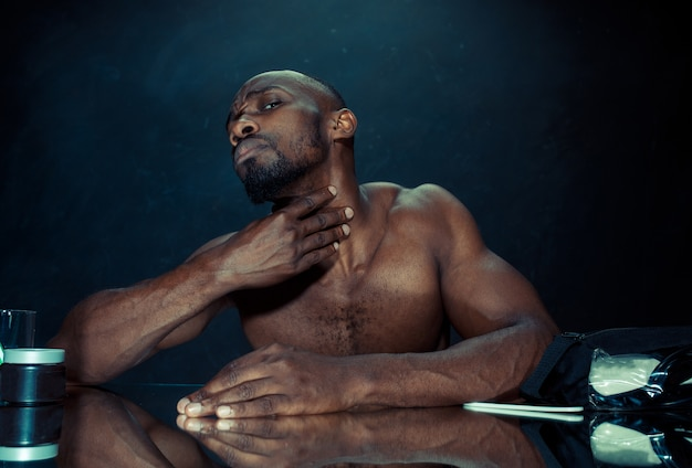 自宅でひげをひっかいた後、鏡の前に座っている寝室の若いアフリカ人。人間の感情の概念