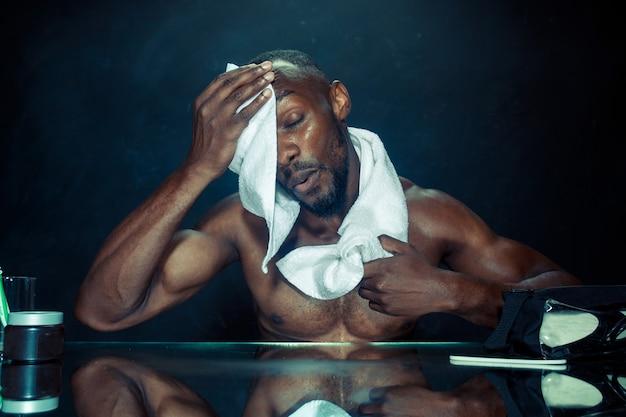 집에서 수염을 긁은 후 거울 앞에 앉아 침실에있는 젊은 아프리카 남자. 인간의 감정 개념