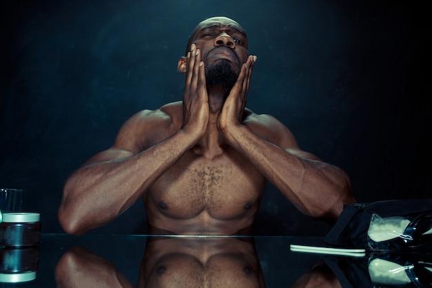 自宅でひげを引っかいた後、鏡の前に座っている寝室の若いアフリカ人。人間の感情の概念