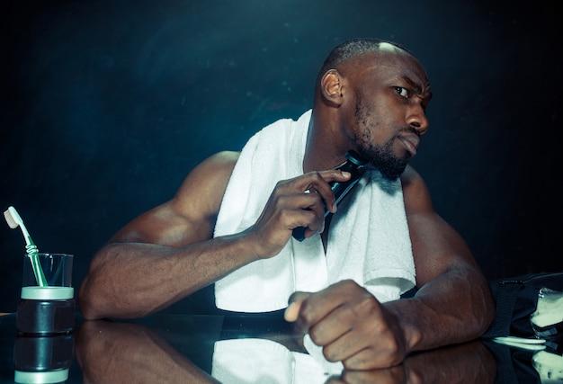 집에서 그의 수염을 긁적 거울 앞에 앉아 침실에서 젊은 아프리카 남자. 인간의 감정 개념