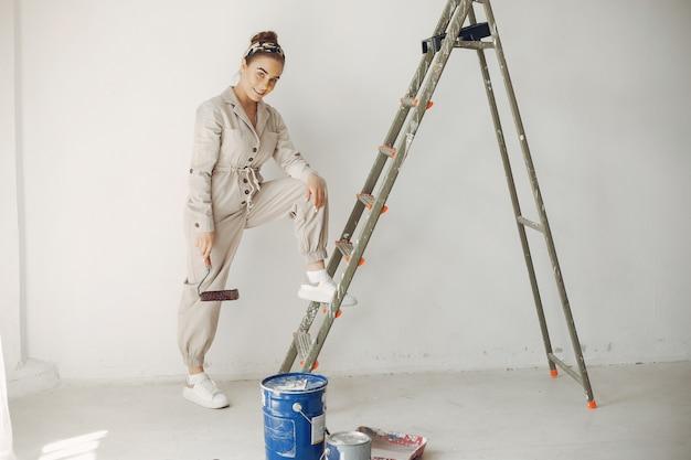 Молодая и милая женщина ремонтирует комнату