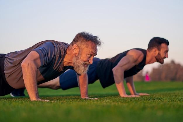 Молодые и старые мужчины вместе отжимаются на траве
