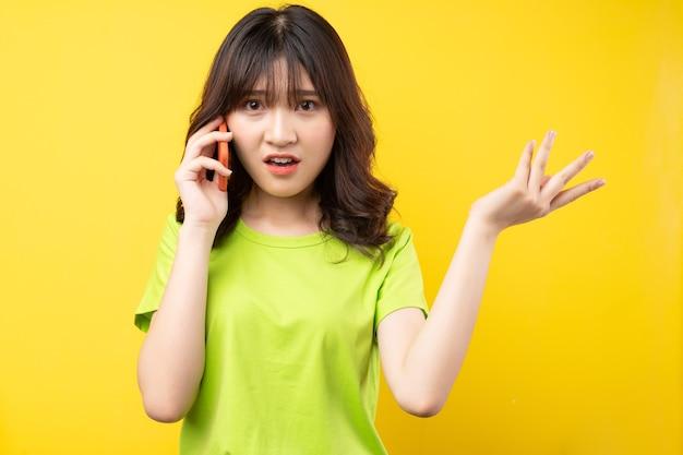 젊은 아시아 소녀는 짜증나는 표정으로 전화를 걸었습니다.