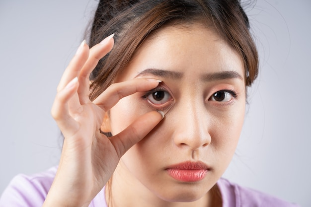 젊은 아시아 여성이 그녀의 손으로 그녀의 눈을 뜨고 있었다