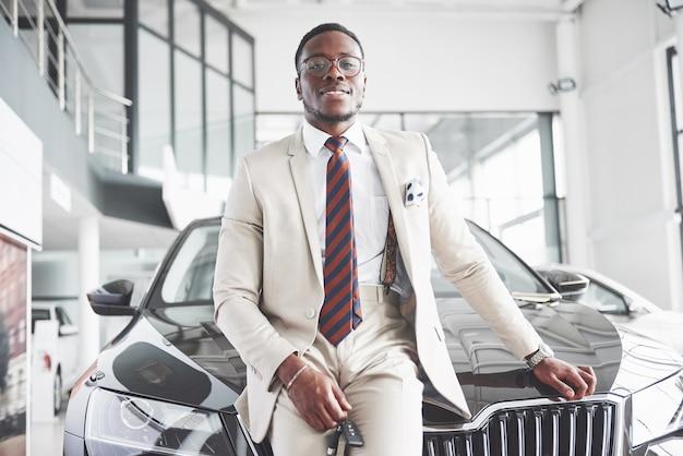 Молодой привлекательный темнокожий бизнесмен покупает новую машину, мечты сбываются.