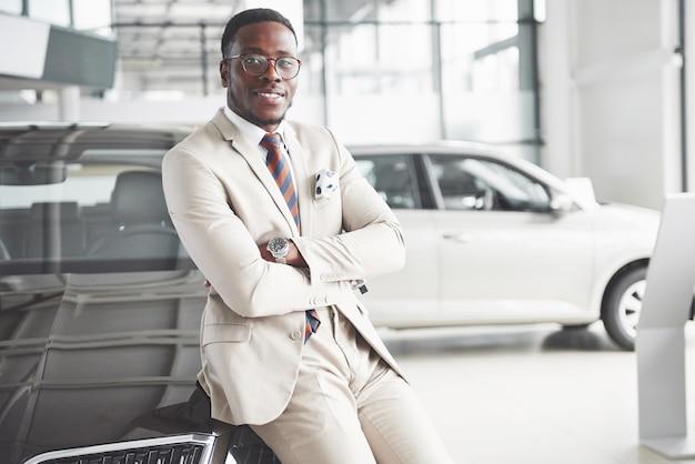 젊은 매력적인 흑인 사업가가 새 차를 사면 꿈이 이루어집니다.